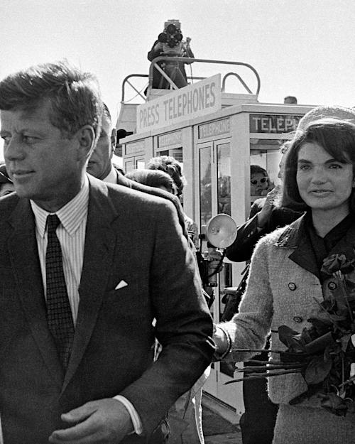 FILE - In this Nov. 22, 1963 file photo, President John F. Kennedy and his wife, Jacqueline Kennedy, arrive at Love Field airport in Dallas, as a television camera, above, follows them. (AP Photo/File)