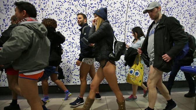 Sejumlah penumpang tanpa mengenakan celana bersiap menaiki kereta selama No Pants Subway Ride ke-18 di London Underground di London, Inggris (13/1). Peringatan ini dilaksanakan setiap tahunnya bermula dari Kota New York, AS. (AFP Photo/Daniel Leal-olivas)