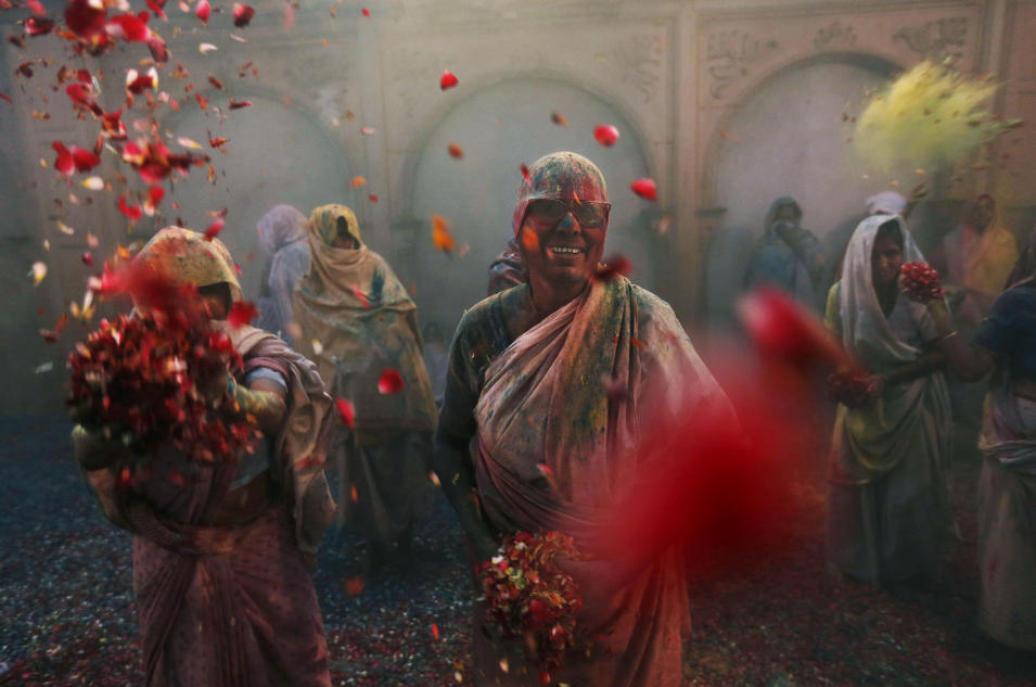 Indian Hindu widows throw flowers as part of Holi celebrations organized by the NGO Sulabh at the Meera Sahbhagini Ashram in Vrindavan, India, Wednesday, March 27, 2013. (AP Photo/Kevin Frayer)