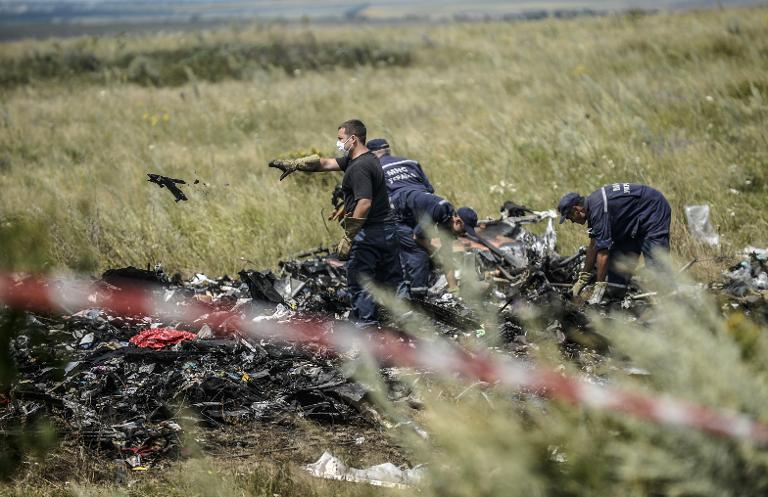 Ukrainian emergency service workers collect bodies of victims at the crash site of Malaysia's flight MH17 in east Ukraine on July 20, 2014