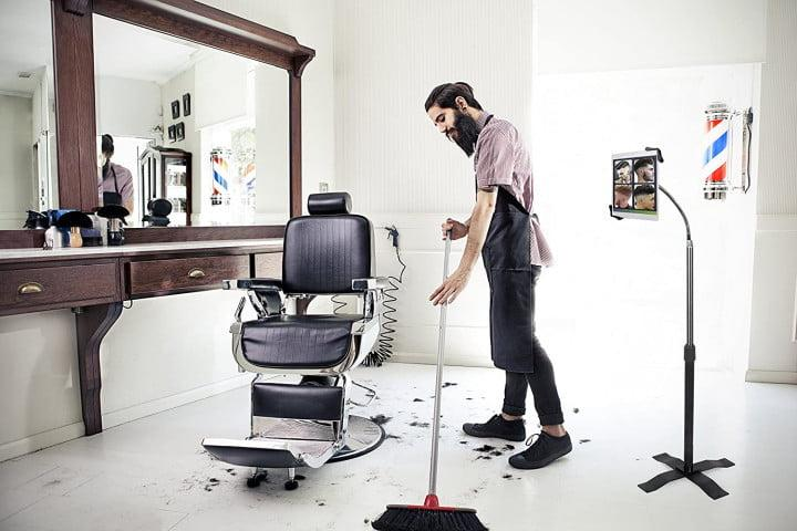 Picture shows a man in a barber shop sweeping hair off the floor while his tablet rests in an upright CTA Digital height-adjustable gooseneck stand