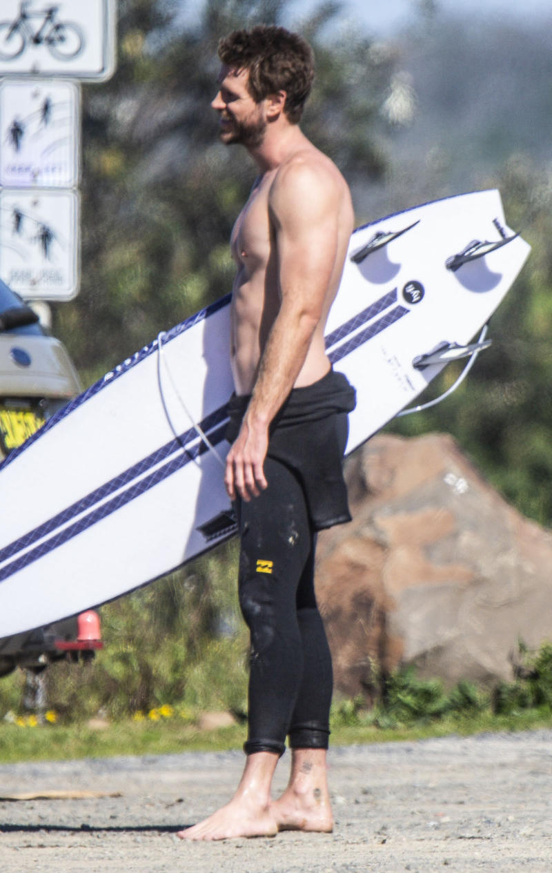 Liam Hemsworth laughs as he holds his surfboard in Byron Bay