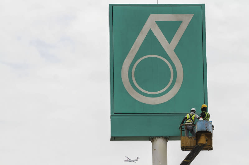 Workers work on a signage bearing a Petronas logo in Kuala Lumpur March 12, 2017. — Picture by Yusof Mat Isa