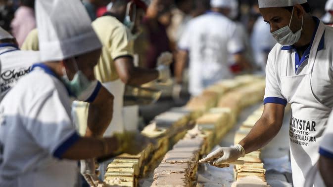 Pembuat roti dan koki menyelesaikan kue sepanjang 6,5 km untuk kue terpanjang dunia, di Thrissur di negara bagian Kerala, India selatan (15/1/2020). Dibutuhkan 12 ribu kilogram gula dan tepung dan menghabiskan waktu lebih dari empat jam untuk membuat kue terpanjang itu. (AFP/Arun Sankar)