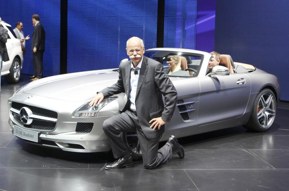 CEO of Mercedes-Benz Dieter Zetsche kneels next to the SLS AMG roadster at the 64th Frankfurt Auto Show in Frankfurt, Germany, Tuesday, Sept.13, 2011. The fair opens its doors to the public from Sept. 15 through Sept. 25, 2011. (AP Photo/Michael Probst)