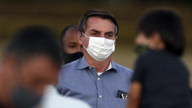 Presiden Brasil Jair Bolsonaro mengenakan masker saat menemui para pendukungnya di luar Istana Alvorada, Brasilia, Brasil, Jumat (24/7/2020). Jair Bolsonaro dinyatakan positif terinfeksi COVID-19 pada 7 Juli lalu. (AP Photo/Eraldo Peres)