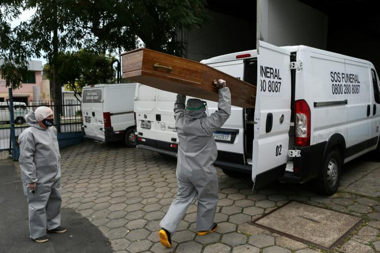 After working for 12 hours on funerals, Izaias Nascimento (R) -- seen here loading the coffin for a COVID-19 victim into a van -- has dinner with his family and then holds evening church services