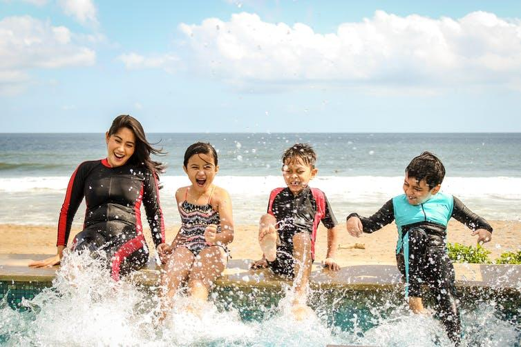 Family splashing in water by the seaside.
