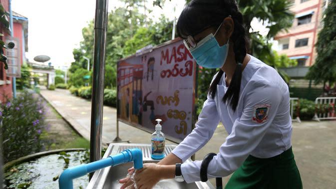 Seorang siswa yang mengenakan masker mencuci tangan di sekolah pada hari pendaftaran sekolah di Yangon, Myanmar (13/7/2020). Myanmar sejak Selasa (7/7) memulai pendaftaran sekolah untuk tahun ajaran 2020-2021, yang tertunda akibat pandemi COVID-19. (Xinhua/U Aung)