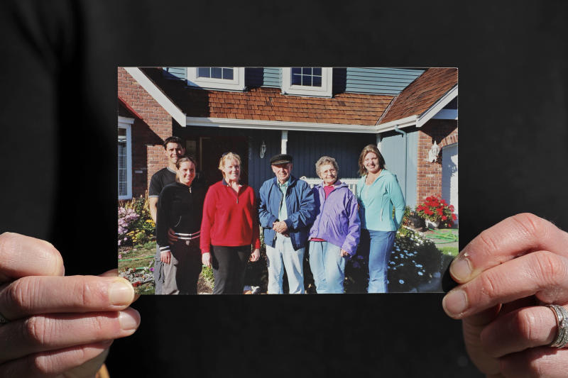 In this Wednesday, April 8, 2020, photo, Kelly Adsero holds a family photo of her grandfather Bill Chambers, center, as he stands with his wife, Barbara Jean, second from right, his daughters Patty, third from left, and Cindy, right, and Adsero and her husband Nick, left. Chambers, 97, died March 14, 2020, at an adult family home where he lived with four other World War II veterans. He wasn't obviously ill, but tested positive for the new coronavirus after he died. (AP Photo/Ted S. Warren)