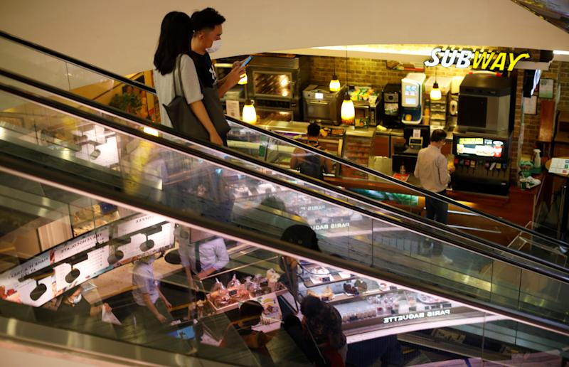 People wearing protective face masks ride an escalator at a shopping mall, amid the coronavirus disease (COVID-19) outbreak, in Singapore July 14, 2020. REUTERS/Edgar Su