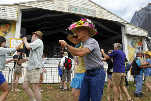 Robert Gale, wearing a festive flowered hat, dances with Liz Lindahl in front of the Fais Do Do Stage during the New Orleans Jazz and Heritage Festival in New Orleans, Friday, April 26, 2013. The Metairie, La. couple were dancing to the music of the Cajun band T'Monde during the opening day of the annual festival. (AP Photo/Doug Parker)