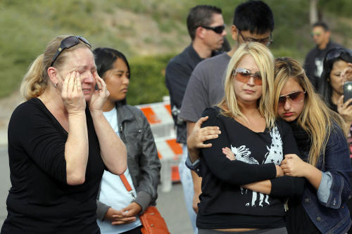 "Amie Kaz, left, and Marjan Bauman and her daughter Alexandra Bauman, right, join others at the site of the auto crash that took the life of actor Paul Walker and another man, in the small community of Valencia, Calif., Monday, Dec. 2, 2013. The neighborhood where ""Fast & Furious"" star Walker died in the one-car crash is known to attract street racers, according to law enforcement officials. Walker and his friend and fellow fast-car enthusiast Roger Rodas died Saturday when the 2005 Porsche Carrera GT they were traveling in smashed into a light pole and tree. The two had taken what was expected to be a brief drive away from a charity fundraiser at Rodas' custom car shop in the Southern California community of Valencia, about 30 miles (48 kilometers) northwest of Los Angeles. (AP Photo/Nick Ut)"