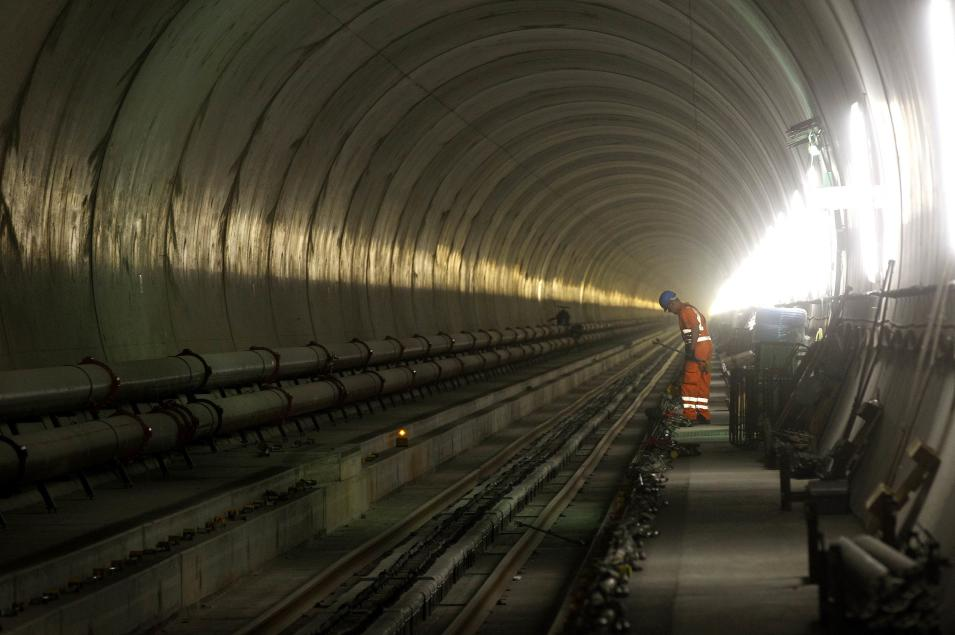 A worker prepares tools and materia during the installation of the railway tracks in the NEAT Gotthard Base tunnel near Erstfeld