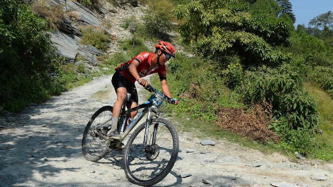 Rohit Thakur dari India bersaing dalam lomba sepeda gunung Himalaya MTB di dekat Mandi, Himachal Pradesh, India utara (4/10). Lomba ini berlangsung selama delapan tahap di kaki pegunungan Himalaya. (AFP Photo/Sajjad Hussain)