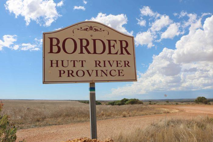 A white and red sign reading 'Border Hutt River Province' stands next to a gravel road under a blue cloudy sky.