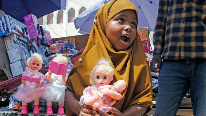Seorang gadis muda memegang boneka yang dibelikan ibunya untuknya di pasar jalanan ketika keluarga berbelanja untuk hari libur Idul Fitri, yang menandai akhir bulan puasa Ramadhan, di Mogadishu, Somalia, (19/5/2020). (AP Photo/Farah Abdi Warsameh)