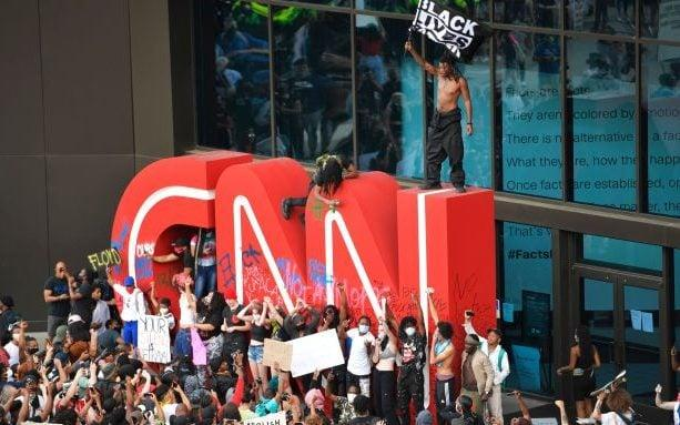 Demonstrators paint on the CNN logo during a protest, in Atlanta, in response to the death of George Floyd in police custody on Memorial Day in Minneapolis. - AP