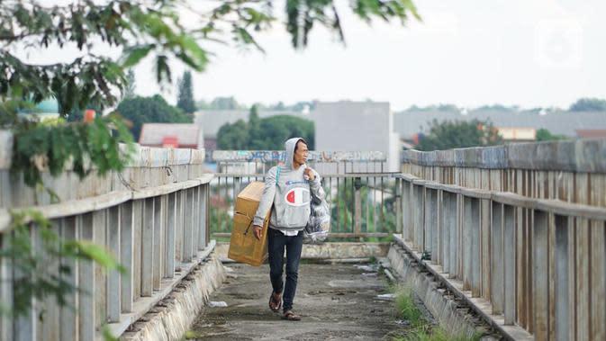 Seorang pria tanpa mengenakan masker melintasi Jembatan Penyeberangan Orang di Kawasan Jakarta, Selasa (19/5/2020). Sanksi PSBB yang kurang tegas menyebabkan sebagian warga masih bebas beraktivitas tanpa masker, meskipun resiko penyebaran virus corona masih tinggi. (Liputan6.com/Immanuel Antonius)