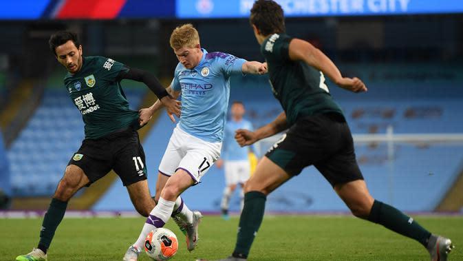 Gelandang Manchester City, Kevin De Bruyne (tengah) berusaha menggiring bola dari kawalan pemain Burnley, Dwight McNeil (kiri) pada pertandingan lanjutan Liga Inggris di Stadion Etihad di Manchester, Inggris (22/6/2020). City menang telak 5-0 atas Burnley. (Michael Regan/POOL/AFP)