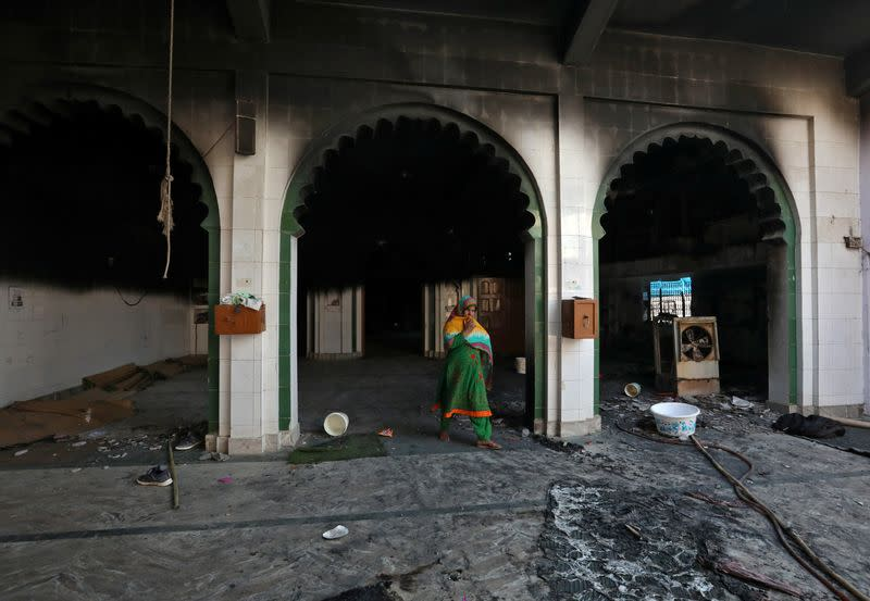 A woman walks inside a partially damaged mosque after it was set on fire by a mob in a riot affected area after clashes erupted between people demonstrating for and against a new citizenship law in New Delhi