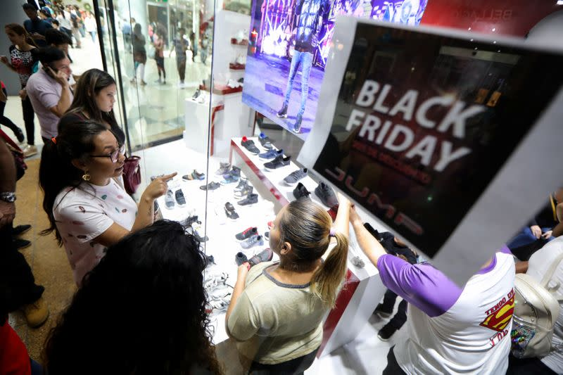 People watch products outside a store at a mall during the Black Friday sales in Caracas