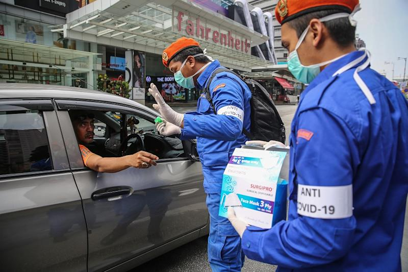 Malaysia Civil Defence Force personnel distribute protective face masks to the public in Kuala Lumpur March 21, 2020. — Picture by Yusof Mat Isa