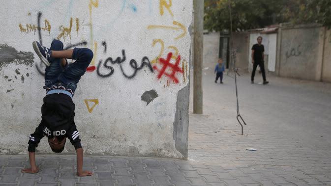 Seorang anak Palestina melakukan pemanasan saat mengikuti pelatihan tari di kamp pengungsi Al-Nusairat, Jalur Gaza tengah (5/11/2019). Pada 2012, Ahmed dan teman-temannya mendirikan sekolah tari di kamp pengungsi Nuseirat. (AP Photo/Hatem Moussa)