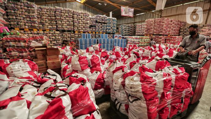 Pekerja memindahkan paket bantuan sosial (bansos) di Gudang Food Station Cipinang, Jakarta, Rabu (22/4/2020). Pemerintah pusat menyalurkan paket bansos selama tiga bulan untuk mencegah warga mudik dan meningkatkan daya beli selama masa pandemi COVID-19. (Liputan6.com/Johan Tallo)
