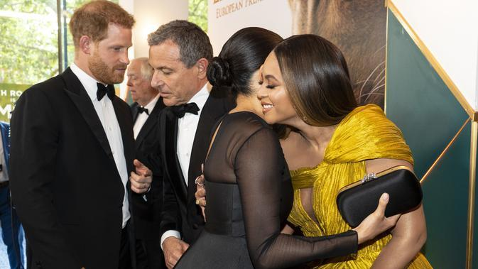 Pangeran Harry menyapa CEO Disney Robert Iger dan Meghan Markle cipika-cipiki dengan Beyonce di premier film The Lion King di London, Inggris, 14 Juli 2019. (NIKLAS HALLE'N / POOL / AFP)
