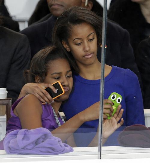 Malia Obama, right, and Sasha Obama look on from the presidential box during the Inaugural parade, Monday, Jan. 21, 2013, in Washington. Thousands marched during the 57th Presidential Inauguration parade after the ceremonial swearing-in of President Barack Obama. (AP Photo/Gerald Herbert)