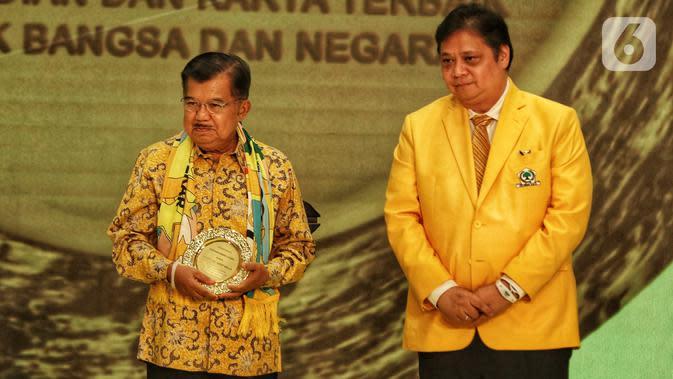 Wakil Presiden Indonesia ke-10 dan ke-12 Jusuf Kalla (kiri) membawa penghargaan didampingi Ketua Umum Partai Golkar Airlangga Hartarto (kanan) dalam peringatan HUT ke-55 Partai Golkar di Jakarta, Rabu (6/11/2019). (Liputan6.com/JohanTallo)