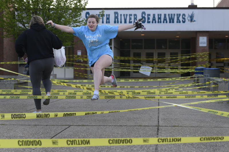 South River High School Class of 2020 senior Aly Yates of Edgewater, Md., jumps over caution tape outside the South River High School in Edgewater, Md., Wednesday, May 13, 2020, as park of a senior prank. Despite the closure of the school because of the coronavirus pandemic, the students are finding ways to keep traditions alive while their family and friends are finding new ways to celebrate and recognize their seniors. (AP Photo/Susan Walsh)