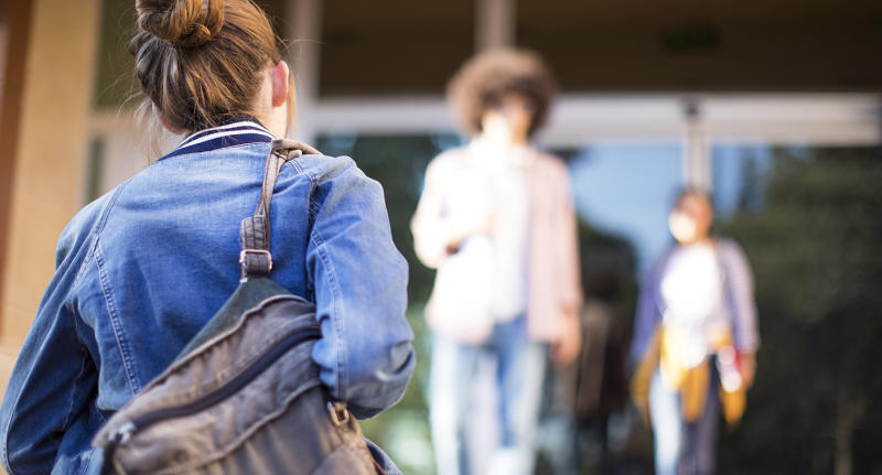 The Queensland tribunal found the teacher had manipulated the 17-year-old student. Pictured is a stock image of a girl facing away from the camera with a backpack slung over one shoulder.