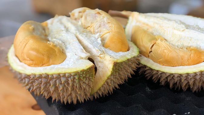 Mengonsumsi Buah Durian (Photo by Jim Teo on Unsplash)