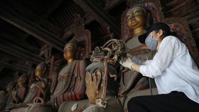 Seorang ahli konservasi peninggalan sejarah merestorasi patung tanah liat yang dicat warna di Biara Fengguo, China (8/6/2020). Pada 2012,
