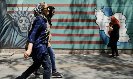 People walk by murals on the wall of the former US embassy in the Iranian capital Tehran on August 7, 2018 after US President Donald Trump warned countries against doing business with Iran