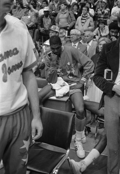 FILE - In this April 5, 1983, file photo, University of Houston's Akeem Olajuwon sits after the last second shot by Lorenzo Charles of North Carolina State won the Final Four championship game game in Albuquerque, N.M. The NCAA and networks across the sports dial have infused fans with a hoops fix by rebroadcasting epic NCAA Tournament games. Coaches and players involved in those games are adding insight and a dash of humor by live tweeting during the replay. (AP Photo/File)