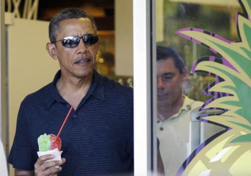 President Barack Obama holds his shave ice as he exits Island Snow to greet people waiting outside, Tuesday, Dec. 31, 2013. The first family is in Hawaii for their annual holiday vacation. (AP Photo/Carolyn Kaster)