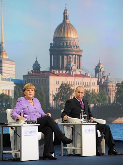 Russian President Vladimir Putin, right, and German Chancellor Angela Merkel attend the economic forum in St. Petersburg, Russia, Friday, June 21, 2013. (AP Photo/RIA-Novosti, Mikhail Klimentyev, Presidential Press Service)