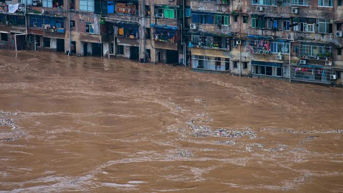 Daerah permukiman yang terendam banjir di Distrik Qijiang, Kota Chongqing, China barat daya (1/7/2020). Guyuran hujan telah menyebabkan peningkatan debit air ke sungai-sungai di daerah pusat kota, dan beberapa pagar pengaman di sepanjang sungai rusak oleh derasnya arus air. (Xinhua/Chen Xingyu)