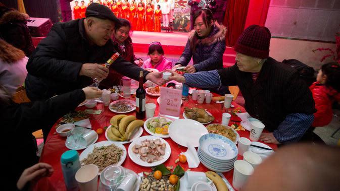 Sebuah keluarga merayakan Tahun Baru imlek dengan makan bersama di sebuah restoran (AP Photo/Ng Han Guan)