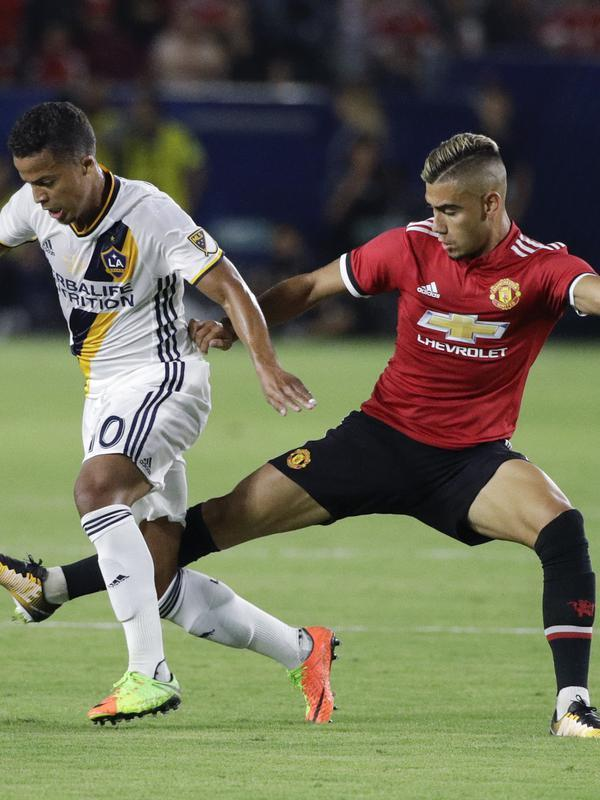 Pemain LA Galaxy, Giovani dos Santos (kiri) berusaha melewati adangan pemain Manchester United, Andreas Pereira pada laga persahabatan di StubHub Center, California, Sabtu (15/7/2017). MU menang 5-2. (AP/Jae C. Hong)