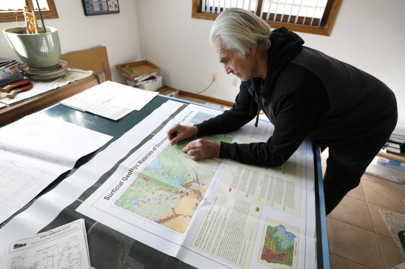 In this Nov. 1, 2018, photo, Gordon Garrison looks over geological maps of land surrounding his farm, in Estherville, Iowa. Garrison sued a nearby operation with 4,400 hogs, contending manure from its croplands fouls a creek that runs through his property and feeds the Des Moines River. (AP Photo/Charlie Neibergall)