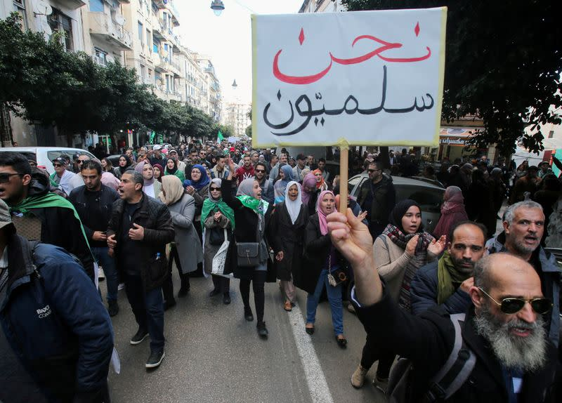 FILE PHOTO: A demonstrator holds a placard during an anti-government rally in Algiers,
