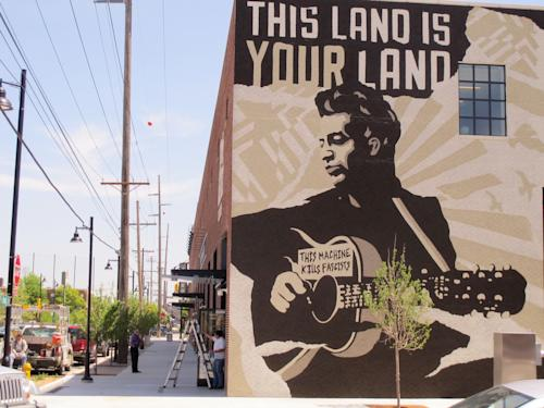 This April 25, 2013, photo shows workers put the finishing touches on the Woody Guthrie Center, which features a mural of the Oklahoma-born folk singer/songwriter, in downtown Tulsa. The center is set to open to the public on Saturday, April 27. (AP Photo/Justin Juozapavicius)