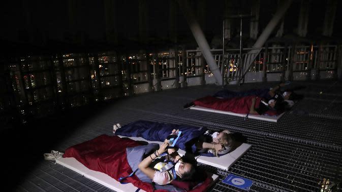 Orang-orang menginap di tempat berkemah semalam di atap gedung pencakar langit di Seoul, Korea Selatan (7/8/2020). Menara Lotte World membuka area berkemah jarak sosial di atap menara dan tanah untuk orang-orang yang jenuh di cuaca musim panas dan Covid-19. (AP Photo/Lee Jin-man)