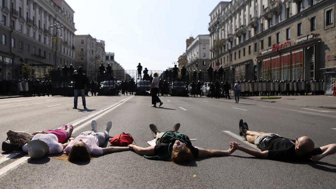 Para pengunjuk rasa berbaring di depan polisi antihuru-hara yang memblokir demonstrasi pendukung oposisi Belarusia di Minsk, Belarusia, Minggu (30/8/2020). Puluhan ribu demonstran berkumpul untuk menuntut agar Presiden Belarusia Alexander Lukashenko mengundurkan diri. (AP Photo)