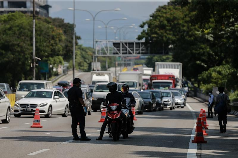 Police personnel are seen at a roadblock at Jalan Kuching in Kuala Lumpur March 28, 2020. — Picture by Ahmad Zamzahuri