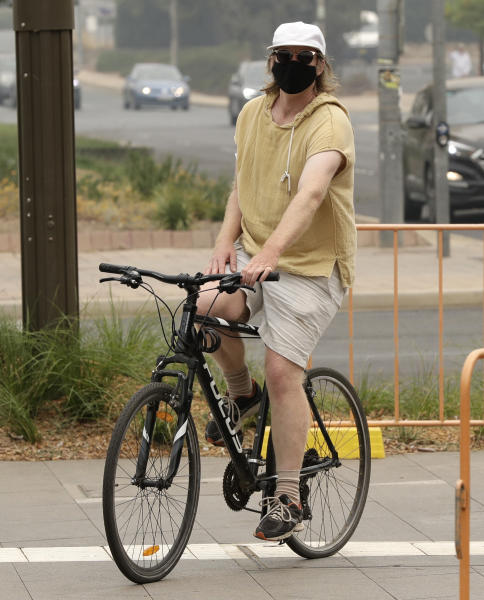 A cyclist wears a mask as smoke shrouds the Australian capital of Canberra, Australia, Thursday, Jan. 2, 2020. Australia deployed military ships and aircraft to help communities ravaged by apocalyptic wildfires that destroyed homes and sent thousands of residents and holidaymakers fleeing to the shoreline. (AP Photo/Mark Baker)